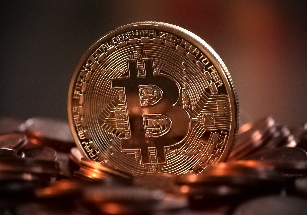 One bitcoin standing up among other bitcoins