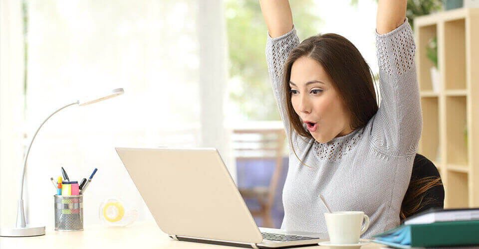 Young woman on laptop happy she was able to remove hard credit inquiries from her credit report.