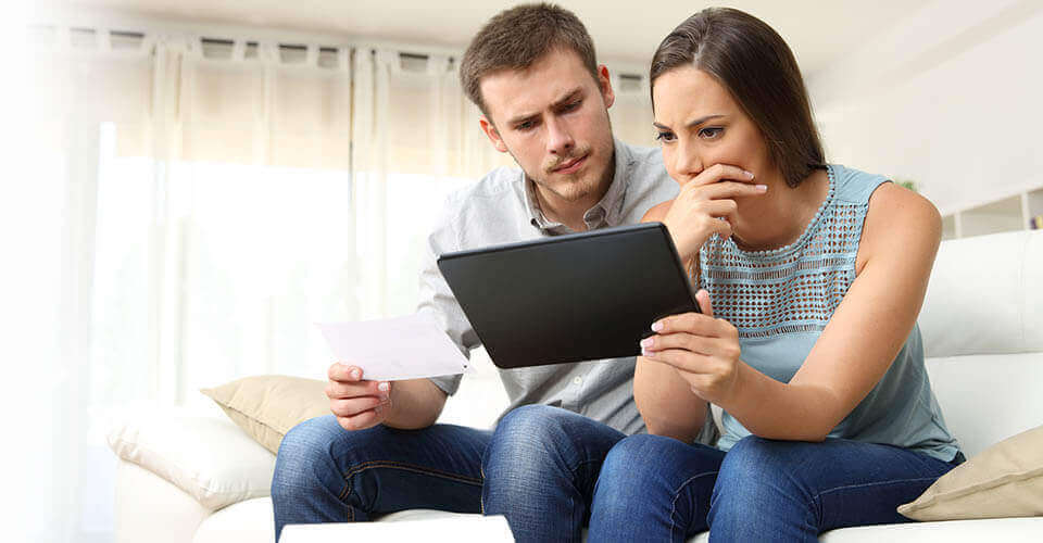 Couple looking at tablet screen for a refund